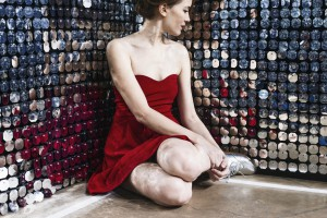 a-woman-in-a-red-dress-sits-and-ponders-a-wall-of-mirrors_925x